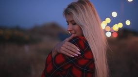 Attractive woman is cold and warming body in field at dusk. Attractive woman is cold and warming her body in field at dusk stock footage