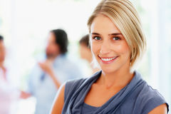 Attractive woman with colleagues in background Stock Photos