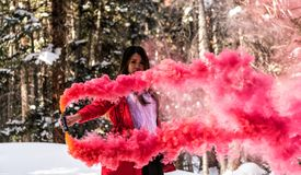 Attractive woman with a colorful smoke grenade stock photography