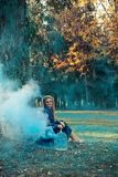 Attractive woman with a colorful smoke grenade bomb fashion stock photos