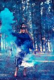 Attractive woman with a colorful smoke grenade bomb fashion royalty free stock photos