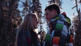 Attractive woman in a colorful winter outfit and handsome young man in green ski-costume. Gorgeous woman standing by the stock footage