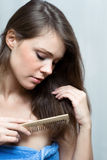 Attractive woman combing her hair.  Royalty Free Stock Photos