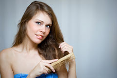 Attractive woman combing her hair. By wooden hairbrush Stock Photography