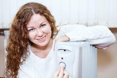 Attractive woman controlling temperature of oil heater Stock Images