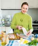 Attractive woman cooking fish Stock Photography