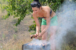 Attractive woman cooking meat on a barbecue Royalty Free Stock Photography