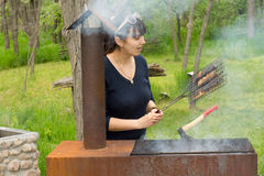 Attractive woman cooking meat over a barbecue Royalty Free Stock Photo