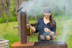 Attractive woman cooking over a picnic BBQ Stock Photography