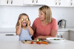 Free Attractive Woman Cooking Together With Her Sweet Beautiful Blond Little 6 Or 7 Years Old Daughter Happy Playful With Cucumber As E Royalty Free Stock Image - 110051286