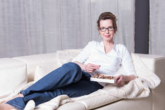 Attractive woman on couch eating chocolate Royalty Free Stock Photo