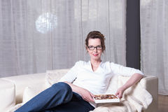 Attractive woman on couch eating chocolate Stock Image