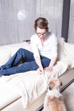 Attractive woman on couch feeding her dog Stock Photo