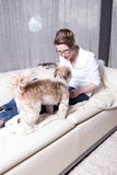 Attractive woman on couch feeding her dog Stock Photography