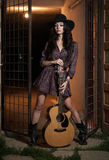 Attractive woman with country look, indoors shot, american country style. Girl with black cowboy hat and guitar Royalty Free Stock Image