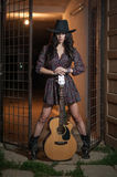 Attractive woman with country look, indoors shot, american country style. Girl with black cowboy hat and guitar. Beautiful brunette with short dress and boots royalty free stock photography