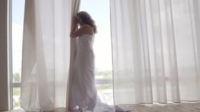 Attractive woman covered in the bedsheet standing near the floor-to-ceiling window and looking away. Leisure indoors. Attractive woman covered in the bedsheet stock video footage