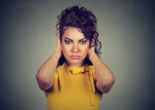 Attractive woman covering with hands her ears looking at camera Royalty Free Stock Photography