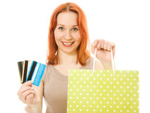 Attractive woman with credit cards and shopping. Attractive red-haired woman with cards and shopping isolated on white Royalty Free Stock Photos