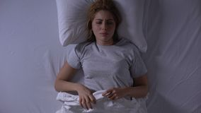 Attractive woman crying lying in her bed at night, female weakness and fragility