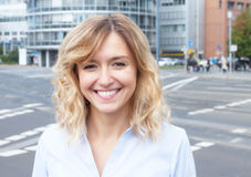 Attractive woman with curly blond hair outside in the city. With streets and buildings in the background Royalty Free Stock Image