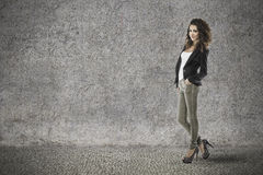 Attractive woman with curly hair on grunge background stock photography