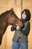 Attractive Woman with Cute Quarter Horse Foal. Pretty dark haired woman standing with her sorrel (chestnut) quarter horse foal against an out of focus barn Stock Images