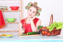 Attractive woman cutting cucumber in the kitchen Royalty Free Stock Image