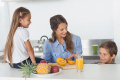 Attractive woman cutting an orange for her children stock photos