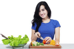 Attractive woman cutting salad Royalty Free Stock Photos