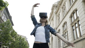 Attractive woman dancing ballet in public place with virtual reality vr headset. Young attractive woman dancing ballet in public place with virtual reality vr stock footage