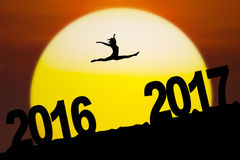 Attractive woman dancing on the hill with numbers. Silhouette of an attractive woman is dancing and jumping between numbers 2016 to 2017 on the hill with sundown vector illustration