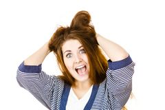 Woman having shocked amazed face expression. Attractive woman with dark brown hair having shocked amazed face expression with wide open mouth touching her hair Stock Photography