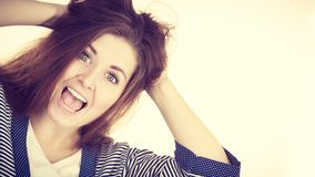 Woman having shocked amazed face expression. Attractive woman with dark brown hair having shocked amazed face expression with wide open mouth touching her hair Royalty Free Stock Image