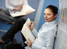 Attractive woman with datebook. Portrait of young woman sitting with datebook on her lap in modern business office building corridor Royalty Free Stock Images