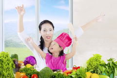 Attractive woman and daughter with vegetables Stock Images