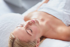Attractive woman at dayspa for skin treatment. Close up shot of attractive young woman lying with her eyes closed on a massage table. Caucasian woman at dayspa Stock Images
