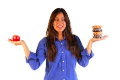 Attractive woman deciding to eat apple or donut. Attractive young woman holding an apple in one hand donuts in the other trying to decide which to eat Stock Photography
