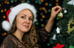 Attractive woman decorates tree Royalty Free Stock Images
