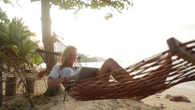 Attractive woman with digital tablet on hammock Royalty Free Stock Image
