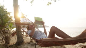 Attractive woman with digital tablet on hammock Royalty Free Stock Images