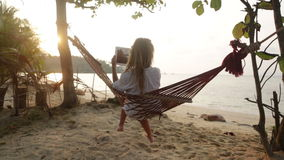Attractive woman with digital tablet on hammock Royalty Free Stock Photos