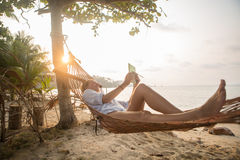 Attractive woman with digital tablet on hammock Stock Image