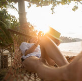 Attractive woman with digital tablet on hammock Stock Photos