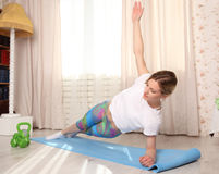 Attractive woman do fitness exercise plank on one hand at home on a blue mat in living room. Attractive blonde woman do fitness exercise at home on a blue mat Royalty Free Stock Photos