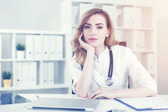 Attractive woman doctor in her office. Portrait of a woman doctor with red hair sitting at her workplace in a white office with a laptop on the desk. Toned image Stock Photo