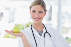 Attractive woman doctor showing an apple. In her hand Royalty Free Stock Images