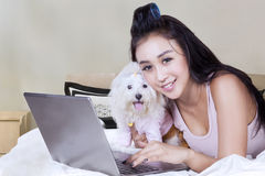 Attractive woman and dog with laptop on bed. Pretty asian woman smiling at the camera while lying in the bedroom with her puppy and laptop Stock Images