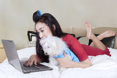 Attractive woman and dog use laptop on bed. Young woman wearing pajama and using laptop with her dog in the bedroom stock photo