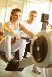 Attractive woman doing exercise on row machine in gym Royalty Free Stock Photo